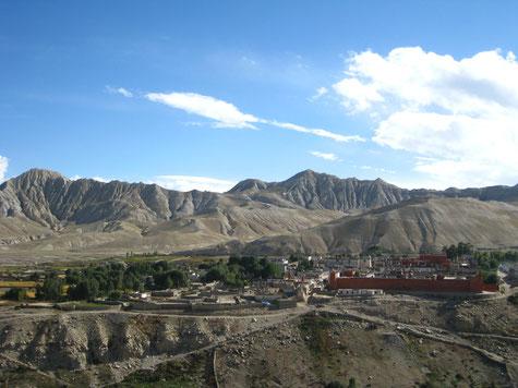 Hauptstadt Lo Manthang, dahinter Berge und blauer Himmel.