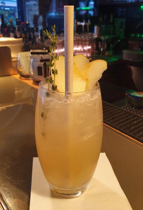 Plunder´s Punch Cocktail (roter Cocktail in einem geschwungenem langen Cocktailglas, mit Dekoration von Ananas und Cocktailkirsche am Spieß)