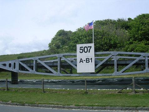In der Zufahrtsstraße zum Omaha Beach ist demonstrativ ein großes Teilstück der Landungsbrücken des bei dem Sturm am 14. Juli zerstörten Mulberry-Hafens aufgestellt.