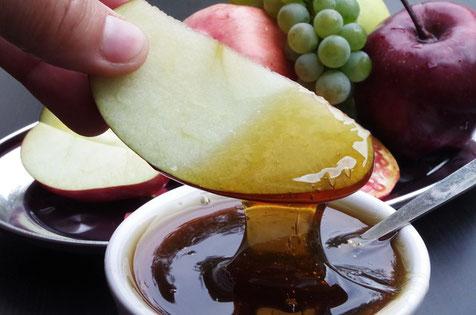 Apfelstückchen in Honig getaucht eignen sich gut als Nachmittags-Snack. (Quelle: Ajale auf pixabay)