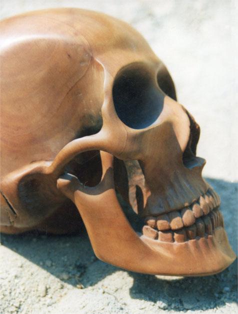 Menschlicher Totenschädel aus Holz geschnitzt. Totenschädel. Hölzerner Schädel. Schädel als Deko Objekt.