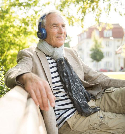 Un monsieur âgé se laisse bercer par la musique dans un parc