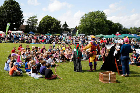 Performers in colourful outfits at Wheathampstead village day in front of a crowd of people sitting on the grass