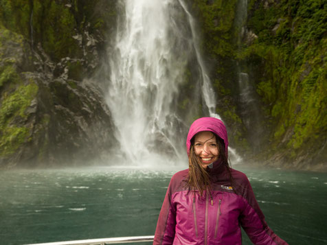 A tourist in front of Stirling Falls in Milford Sound
