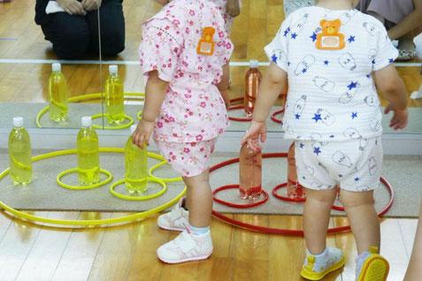 夏祭りの輪投げコーナーで1歳児が輪投げを楽しんでいます。ピンに近づいて、輪を入れたり、工夫して、輪投げをしています。