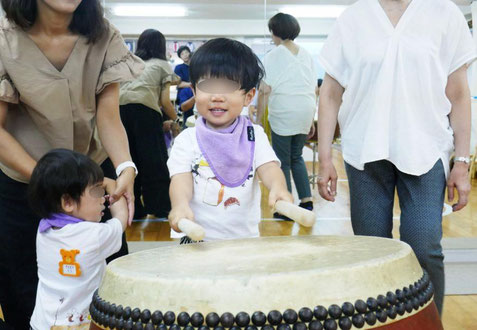 1歳児が和太鼓を体験。バチで太鼓をたたきくと大きな音が出るのが楽しい様子です。