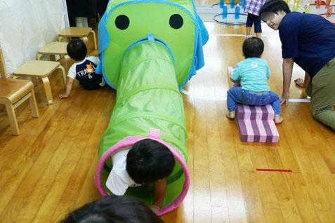 夏祭りの遊びの中の象さんのトンネル遊びを、0歳児や1歳児が全身を使って楽しんでいます。
