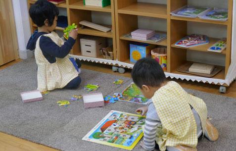 モンテッソーリの活動で、2才児二人がパズルに夢中になっています。