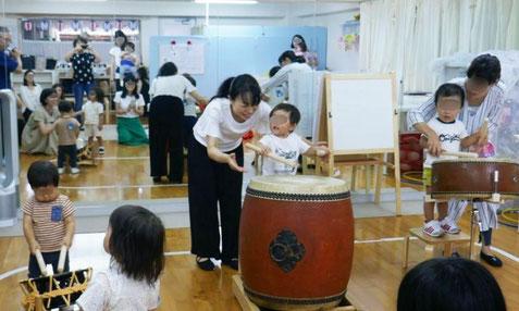 幼児教室の夏祭りで太鼓体験。1歳児がいろいろな和太鼓を叩いて、音が出るのを楽しんでいます。