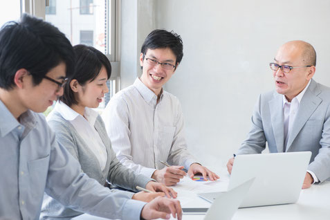 強みを活かした経営をおこなっている中小企業経営者と社員のイメージ
