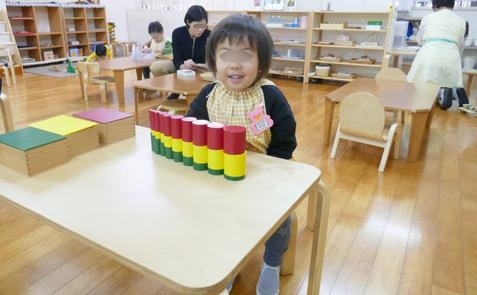 モンテッソーリ活動で、2才児が3種類の色付き円柱を立体的に組み合わせました。