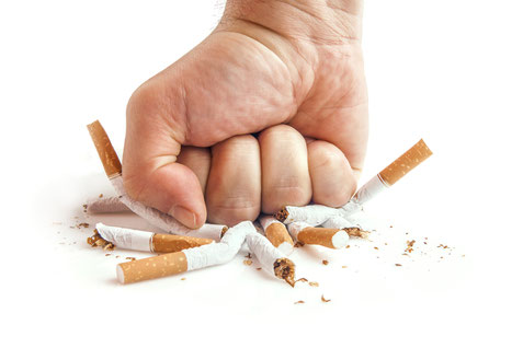 Eine Faust zerschlägt Zigaretten. Mit einer Raucherentwöhnung sagen Sie den Zigaretten ab.