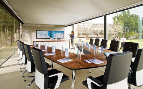 Besprechungszimmer mit Bürostühlen und einem großen Tisch mit Büromöbeln