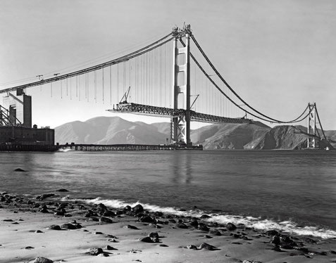 Old photo of Golden Gate bridge under construction, taken from nearby beach.  Exact date unknown, circa 1935.
