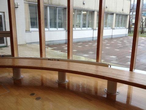明日中等教育学校の広々とした木の廊下に木のベンチとテラス
