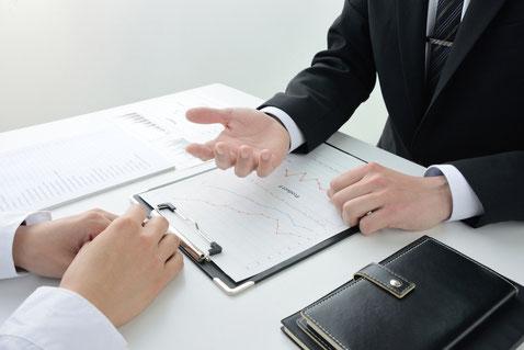データを元にクライアントに説明をするスーツの男性
