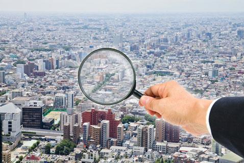 虫眼鏡を持ち街を覗くスーツの男性の手