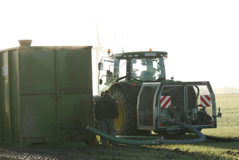 Verschlauchen ,Schlepper mit Pumpstation und Kompressor am Güllecontainer