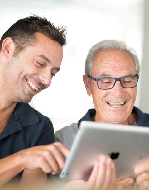 Un monsieur âgé rit de tout cœur avec son soignant