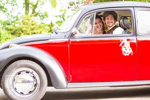 Hochzeitspaar im alten VW Käfer in Wehrheim am Taunus fotografiert durch den Hochzeitsfotografen.