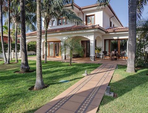 Grüner Vorgarten mit Rasen und vielen Palmen vor der Villa.