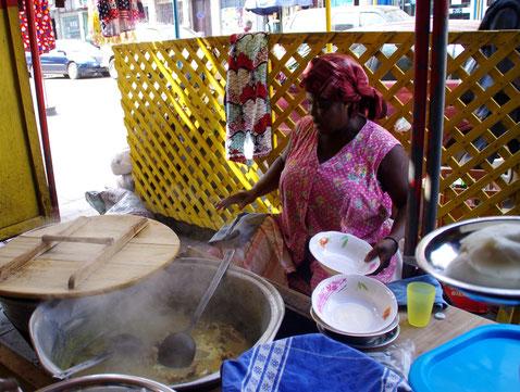 Afrikanerin in Straßenküche in Togo hinter großem Kochtopf und Geschirr sitzend