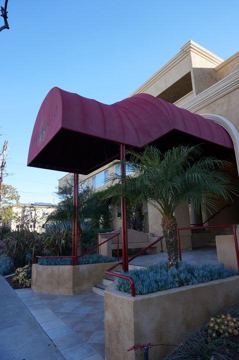 赤いテント屋根が特徴的な建物。曲線と直線がうまく使われており、植物の使い方もとても面白い。