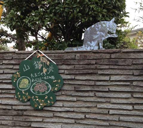 猫の造型は、後ろの緑を描くことでその場に溶け込む。本間純氏の作品