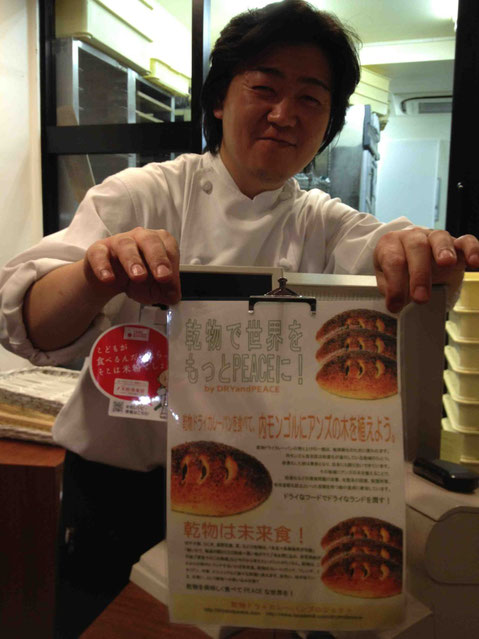 乾物ドライカレーパンプロジェクトのチラシを手に微笑む和良の高橋さん