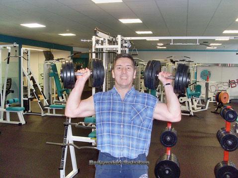 Personal -Trainer Bodymaker Kurzhantelschulterdrücken im Stehen