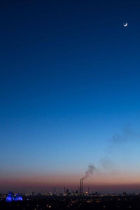 """Duisburg Schwelgern, Klärwerk Emschermündung, Blaue Stunde mit Mond. Von der Halde """"Hühnerheide"""", Oberhausen"""
