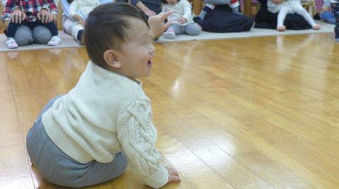幼児教室のリトミックで、0歳児が先生のピアノに楽しく反応しています。