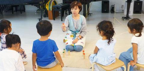 モンテッソーリ感覚教具「雑音筒」で、一番弱い音に集中して聴いている幼稚園児(3歳~5歳)