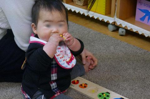幼児教室の親子で学ぶ0歳児コースのモンテッソーリの活動で、0歳児が玩具を口で確かめています。