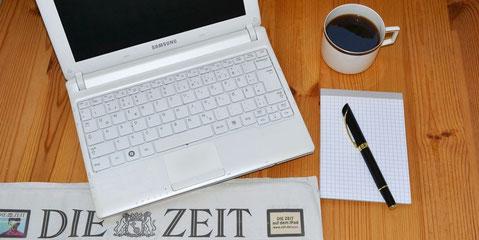 Auf einem Holztisch steht ein Netbook und eine Tasse Kaffee. Stift, Schreibblock und Zeitung liegen bereit.
