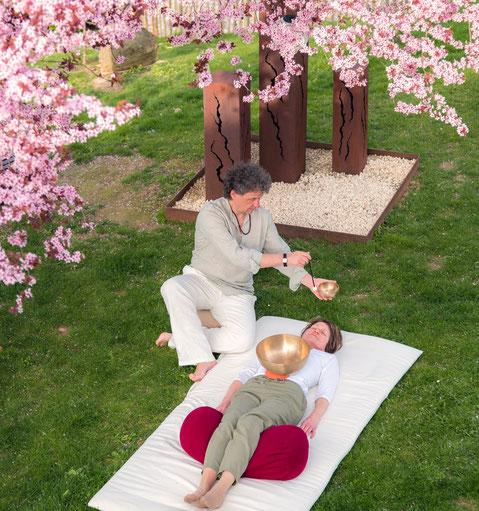 Klangschalenmassage mit Dieter Monsieur unter blühendem Baum