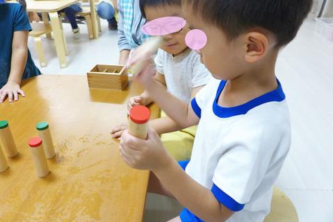 幼稚園児がモンテッソーリ教育の感覚教具「雑音筒」を使って音の強さを確認しながら、聴覚を洗練させています