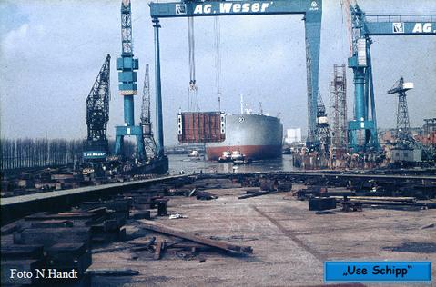 """Der Tanker ist kaum vom Stapel gelaufen bringt der Bockkran schon eine Schiffsverlängerung für ein DDG """"Hansa"""" Frachter,  der im Dock liegt"""