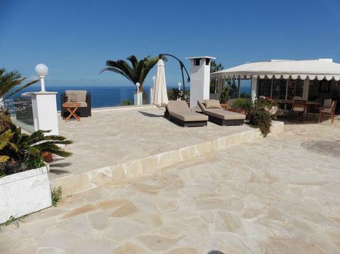 Große geflieste Dachterrasse mit Caport,Liegestühle und gigantischen Blick auf das Meer.