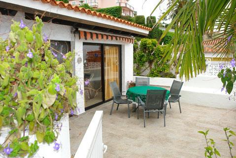 Blick über einen mit  Geranien bepflanzenden Einfassung von der Terrasse auf das Ferienhaus welches rechts und links mit Palmen eingefasst ist.