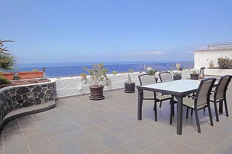 Große geflieste Terrasse mit Pflanzbeete und Meerblick