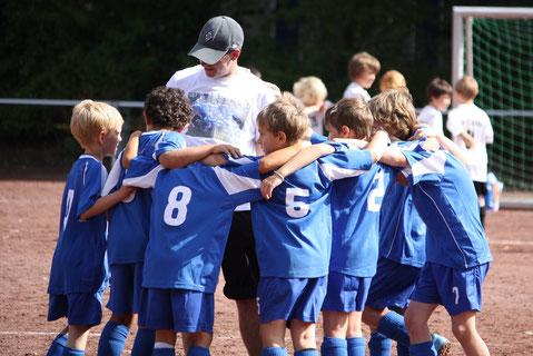 Niños jugando al fútbol reunidos con el entrenador