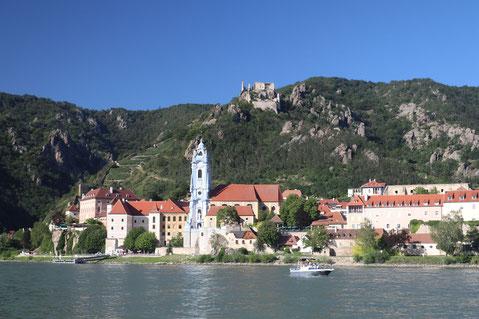 Dürnstein in der Wachau vom gegenüberliegenden Ufer der Donau aus mit markantem blauem Kirchturm und grün bewachsenen Felsen in Hintergrund