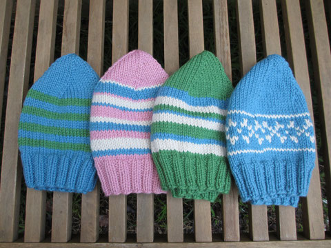 Three variously stripy beanies in blue, green, cream, pink, and one blue beanie with simple cream colourwork.