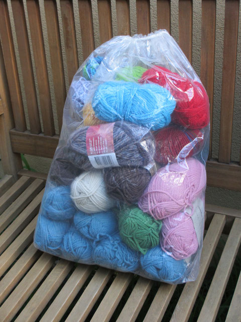 A large plastic bag full of multi-coloured yarns.