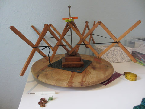 Hand-made wooden umbrella swift, with pegs and elastic holding it in position.