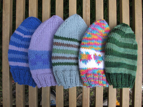 a row of five hats of various sizes, in stripes and basic colourwork