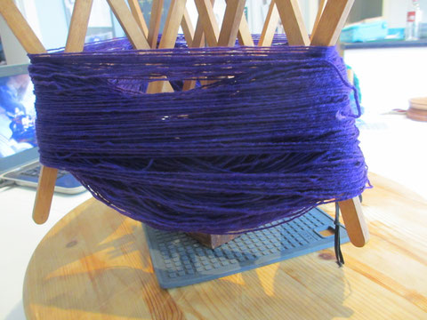 Sagging purple skein of yarn on the swift