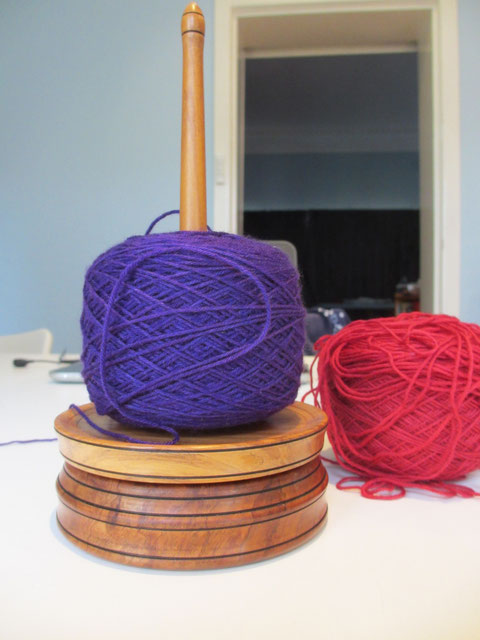 A ball each of purple and red yarn, wound under tension.