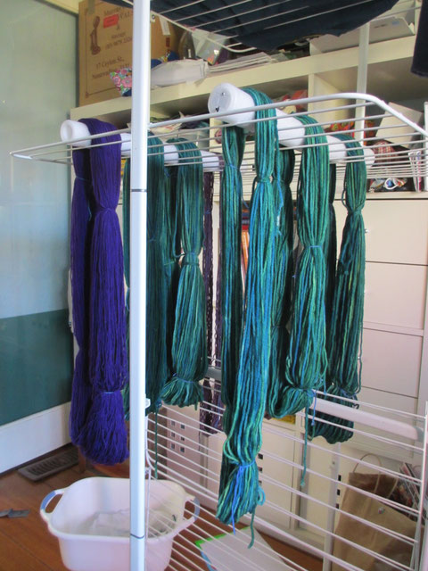 Skeins of green and purple yarns, hanging to dry from a drying rack.